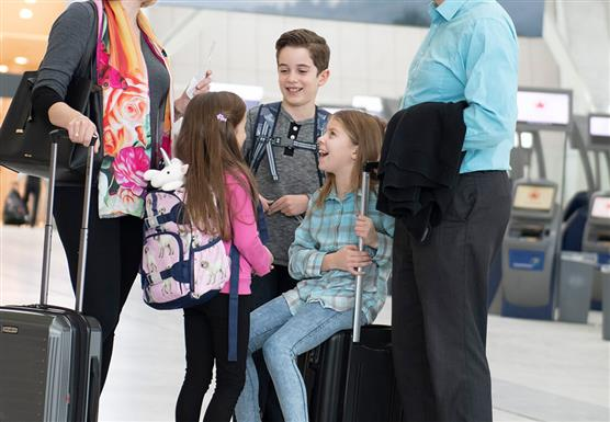 Family carrying bags and travelling through Pearson.
